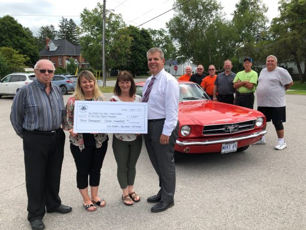 cheque presentation infront of red car