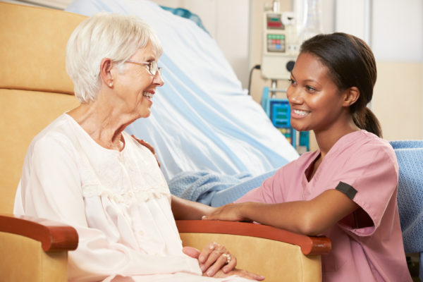 woman in chair with nurse to her side